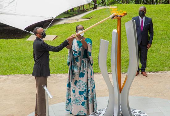 Rwandan President Paul Kagame (L) and first lady Jeannette Kagame light the Flame of Remembrance for the 27th commemoration of the 1994 genocide against the Tutsi, at the Kigali Genocide Memorial in Kigali, capital city of Rwanda, on April 7, 2021. The central African nation on Wednesday began the annual national commemoration for over 1 million victims that lasts for three months, including a mourning week at the beginning. More than 500 Rwandans, friends of Rwanda, members of diplomatic corps gathered in Kigali's indoor sports complex, Kigali Arena, for the ceremony, which invited fewer people than previous years due to the COVID-19 pandemic. (Photo by Cyril Ndegeya/Xinhua)