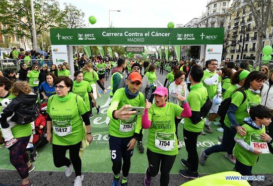 Runners reach the finishing line of the Madrid Race in March Against Cancer in Madrid, Spain, April 15, 2018. The race was held by the Spanish Association Against Cancer, with the purpose of raising public attention on anticancer and having healthy lifestyle. (Xinhua/Guo Qiuda)