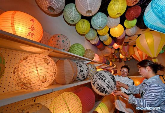 Staff workers discuss the design of paper lanterns at a factory in Jian'ou City, southeast China's Fujian Province, Nov. 4, 2018. Paper lanterns produced by local enterprises and workshops are now exported to markets in Europe, North America and Southeast Asia. (Xinhua/Zhang Guojun)