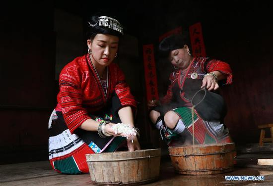 Women make the natural shampoo of fermented rice water in Huangluo Village of the Yao ethnic group in Longji Township of Longsheng County, south China's Guangxi Zhuang Autonomous Region, July 4, 2019. Women here have the tradition of keeping long hair. They use fermented rice water- the water after rinsing rice- together with natural ingredients such as tea seeds and orange peels to wash their hair. The natural shampoo keeps their hair healthy, smooth and shiny. (Photo by Liu Jiaoqing/Xinhua)