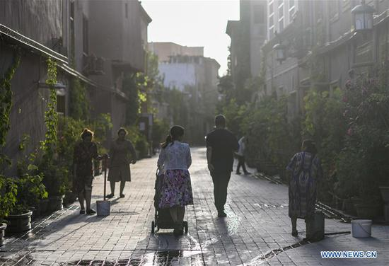 People stroll on the street in the morning at the ancient city of Kashgar, northwest China's Xinjiang Uygur Autonomous Region, July 9, 2019. In the first half of 2019, the ancient city of Kashgar received over 310,000 visits. (Xinhua/Zhao Ge)