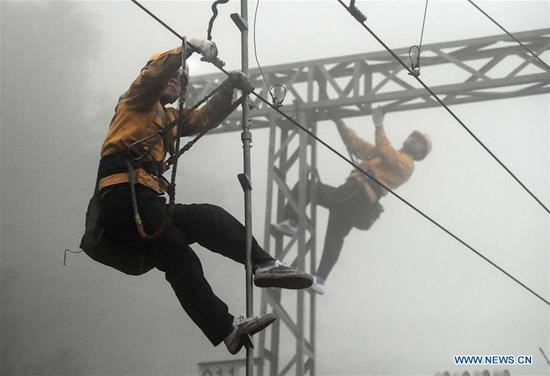 Workers conduct safety check during an overhaul of the overhead line system at a section of the Nanning-Kunming railway in Baise City, south China's Guangxi Zhuang Autonomous Region, Jan. 15, 2020. Workers here were occupied with the overhaul work of overhead line system along Nanning-Kunming railway to ensure traffic safety during the Spring Festival travel rush. (Xinhua/Zhang Ailin)