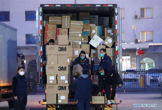 Staff members carry medical goods for Wuhan City of Hubei at Beijing Capital International Airport in Beijing, capital of China, Jan. 27, 2020. A team comprised of 136 medical workers from Beijing left for Wuhan City on Monday to aid the novel coronavirus control efforts there. (Xinhua/Zhang Yuwei)