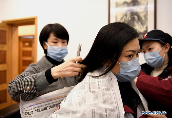 Hu Rong, a medical staff, has her long hair cut to better wear protective products before leaving for Wuhan of Hubei Province, at the airport in Chengdu, capital of southwest China's Sichuan Province, Feb. 2, 2020. The 3rd batch of 126 medical staff of Sichuan Province left for Wuhan on Sunday to aid Hubei Province in fighting the novel coronavirus. (Xinhua/Wang Xi)