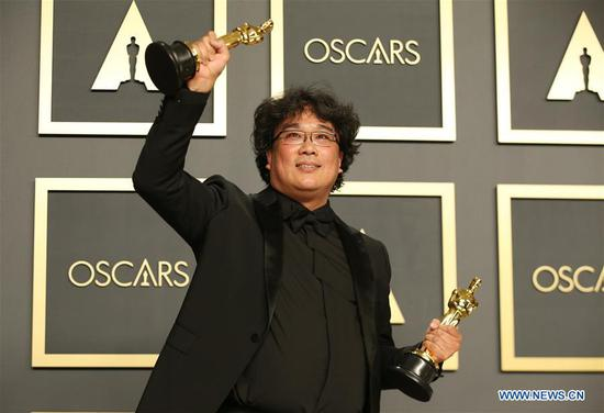 "Bong Joon-ho poses for photos at the 92nd Academy Awards ceremony at the Dolby Theatre in Los Angeles, the United States, Feb. 9, 2020. South Korean black comedy ""Parasite"" turned out to be the biggest winner at the 92nd Academy Awards ceremony on Sunday night. Besides nabbing Best Picture, the genre-bending class thriller also won Best Director for Bong Joon-ho, Best International Feature Film and Best Original Screenplay. ""Parasite"" also made history at the 92nd Academy Awards by becoming the first foreign-language film to win best picture. (Xinhua/Li Ying)"