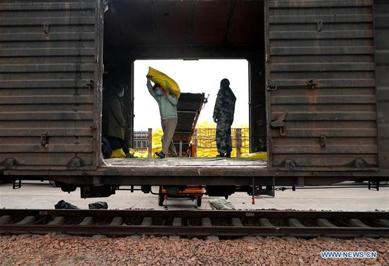 Crew members load spring ploughing materials onto a freight train at the Kaifeng Railway Station in Kaifeng, central China's Henan Province, Feb. 13, 2020. The Kaifeng Railway Station, affiliated to China Railway Zhengzhou Group Co., Ltd, has rolled out active precaution measures while organizing crew members to resume work gradually amid the national fight against the novel coronavirus outbreak. A
