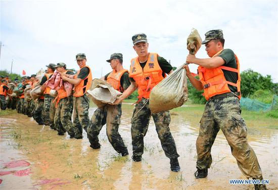 Armed policemen move sand bags for dyke reinforcement in Poyang County, east China's Jiangxi Province, July 12, 2020. Poyang Lake, China's largest freshwater lake located in the eastern province of Jiangxi, has seen its water level rise to a record high on Sunday, according to the provincial department of water resources. At around 12:00 a.m. Sunday, the water level at the lake's Xingzi hydrological station rose to 22.53 meters, 0.01 meters higher than the record in 1998, and continued going up, said the department. (Photo by Cao Xianxun/Xinhua)