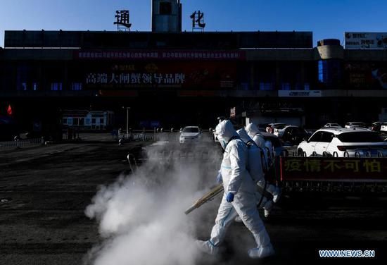 Staff members disinfect the square in front of the railway station of Tonghua City, northeast China's Jilin Province, Feb. 9, 2021. (Xinhua/Xu Chang)
