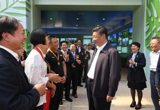 Chinese President Xi Jinping, also general secretary of the Communist Party of China Central Committee and chairman of the Central Military Commission, talks with model workers and representatives of different occupations at a plaza of the Hainan Museum in Haikou, south China's Hainan Province, April 13, 2018. Xi made an inspection tour in Hainan from Wednesday to Friday. (Xinhua/Li Xueren)