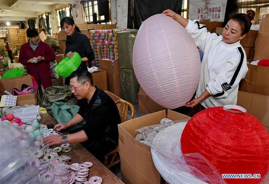 Staff workers check the quality of paper lanterns at a factory in Jian'ou City, southeast China's Fujian Province, Nov. 4, 2018. Paper lanterns produced by local enterprises and workshops are now exported to markets in Europe, North America and Southeast Asia. (Xinhua/Zhang Guojun)