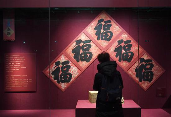 A tourist looks at exhibits displayed at the Palace Museum, also known as the Forbidden City in Beijing, capital of China, Jan. 7, 2019. In celebrating of the most magnificent of all traditional holidays, the Palace Museum presents exhibition of