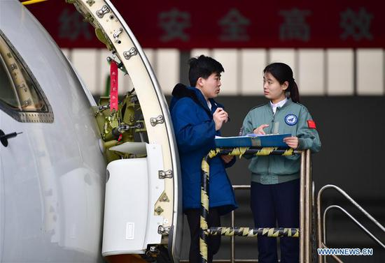 Jiang Dandan (R) discusses flight-test affairs with a crew member in Yanliang District of Xi'an, capital of northwest China's Shaanxi Province, on March 5, 2019. Jiang Dandan, 29, is one of the youngest test pilots in China and the only female test pilot for commercial transport aircrafts currently being trained at the Aviation Industry Corporation of China, Ltd. She went through dozens of professional courses and 750 hours of flying practice in six years. At the end of 2017, she became a test pilot and participated in the test flights during the research and development of ARJ21-700, C919 and other types of aircrafts. (Xinhua/Shao Rui)