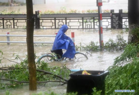 A woman wades through a waterlogged street in Wenling, east China's Zhejiang Province, Aug. 10, 2019. China's National Meteorological Center issued an orange alert for Typhoon Lekima on Saturday morning, as it landed in east China's Zhejiang Province. At around 1:45 a.m., the center of Typhoon Lekima, the ninth typhoon of the year, made landfall in the city of Wenling in Zhejiang, with a maximum wind force of 187 km/h. The super typhoon weakened to a typhoon at 5 a.m. at a maximum wind force of 144 km/h. (Xinhua/Han Chuanhao)