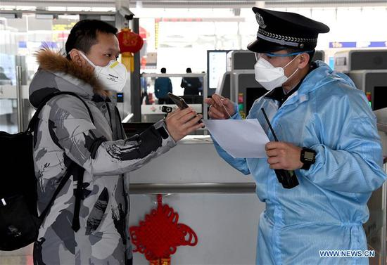 A railway policeman checks a passenger's identity and travel information at Zhengzhou East Railway Station in Zhengzhou, central China's Henan Province, Feb. 1, 2020. Zhengzhou East Railway Station has recently strengthened its efforts to prevent and control the spread of novel coronavirus during the Spring Festival travel rush. (Xinhua/Li An)