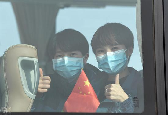 Medics supporting virus-hit Hubei Province gestures on the bus at Guiyang Longdongbao International Airport in Guiyang, southwest China's Guizhou Province, March 20, 2020. Medical assistance teams from Guizhou, which consists of 433 members, left Hubei Province as the epidemic outbreak in the hard-hit province has been subdued. (Xinhua/Yang Wenbin)
