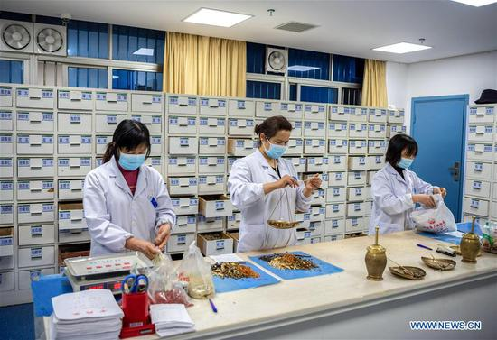 Medical workers prepare traditional Chinese medicine at a hospital in Zigui County of Yichang, central China's Hubei Province, March 27, 2020. The normal medical services in Zigui have been gradually resumed as the coronavirus epidemic wanes. (Photo by Wang Jiaman/Xinhua)