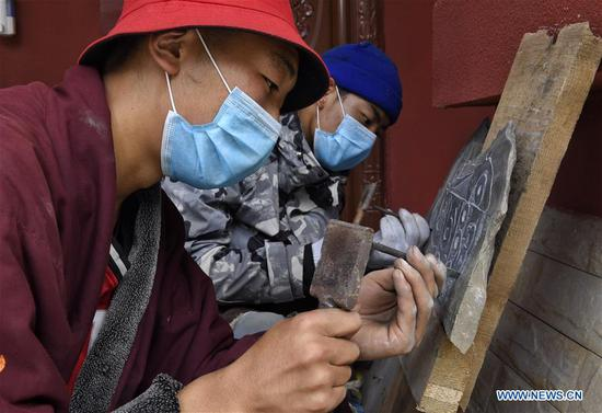 Villagers carve a stone that will be sold as an artwork at a stone carving park in Rangtang County of Aba Tibetan and Qiang Autonomous Prefecture, southwest China's Sichuan Province, June 13, 2020. Located in northwest of Sichuan Province, with nearly one million population, Aba Tibetan and Qiang Autonomous Prefecture has a diversity of ethnic minority groups, including Tibetan, Qiang and Hui, etc. In recent years, to better inherit the ethnic culture, local schools have introduced more traditional cultural courses while local authorities set up training workshops about intangible cultural heritage to help local villagers learn traditional crafts, as a way to boost their incomes. In 2018, the production value of cultural industry in this prefecture has reached about 1.2 billion yuan (about 169.8 million U.S. dollars), accounting for 3.32 percent of gross domestic product (GDP) of this prefecture. (Xinhua/Liu Kun)
