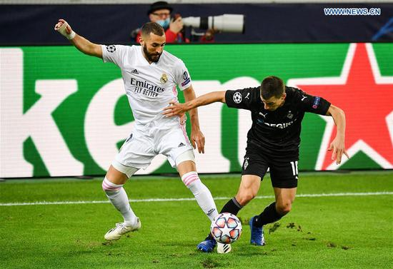Karim Benzema (L) of Real Madrid vies with Stefan Lainer of Moenchengladbach during the UEFA Champions League Group B football match between Real Madrid and Borussia Moenchangladbach in Moenchangladbach, Germany, Oct. 27, 2020. (Photo by Ulrich Hufnagel/Xinhua)