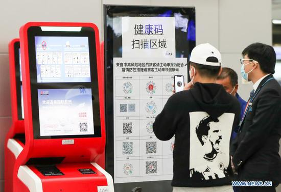 Passengers perform self-service personal health confirmation at Terminal 2 building of the Shanghai Pudong International Airport in east China's Shanghai, Nov. 24, 2020. The airport's recent daily throughput maintains at around 1,000 flights, with passengers wearing face masks and orderly moving in and out. (Xinhua/Ding Ting)