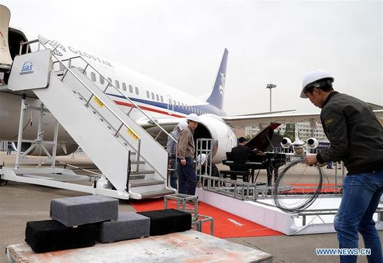 Exhibitors work near aircrafts to be displayed in the Asian Business Aviation Conference and Exhibition (ABACE) at Shanghai Hongqiao International Airport in east China's Shanghai, April 16, 2018. The ABACE is expected to be held here from April 17 to 19, attracting over 170 companies around the world to participate in the exhibition. (Xinhua/Chen Fei)