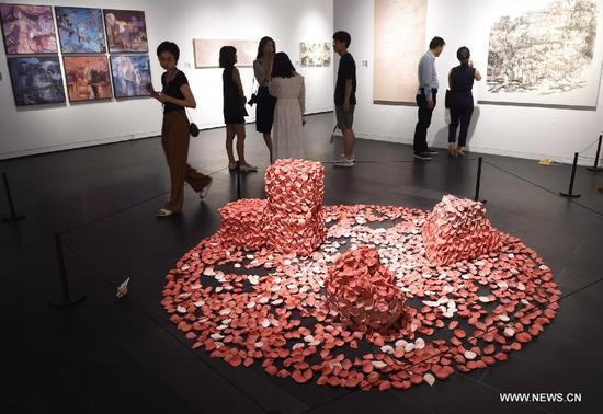 People visit a graduation exhibition of undergraduates of Tsinghua University Academy of Arts and Design in Beijing, capital of China, June 12, 2018. More than 500 pieces (sets) of works were displayed at the exhibition. (Xinhua/Luo Xiaoguang)