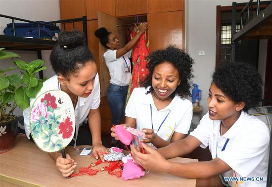 Ethiopian workers of ANTEX Fashion Group look at Chinese handicrafts at their dormitory in Huzhou, east China's Zhejiang Province, Aug. 30, 2018. In 2017, Zhejiang's ANTEX Fashion Group set a branch in Ethiopia. To build a better team, the Ethiopian branch has sent 93 Ethiopian workers to China for six-month training. Besides learning production skills, these workers also learnt Chinese language, calligraphy and martial art in spare time.