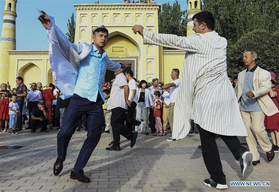 People dance to music during Corban Festival celebrations in Kashgar, northwest China's Xinjiang Uygur Autonomous Region, Aug. 11, 2019. The Corban Festival, also known as Eid al-Adha or the feast of the sacrifice, falls on Sunday. (Xinhua/Wang Fei)