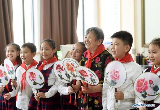 Ying Miaofang and primary school students display moon-shaped fans they made in Zhuji City, east China's Zhejiang Province, Oct. 6, 2019. Ying Miaofang, 80, is widely known for her warm-heartedness. An illustration is the assistance Ying provided for college students to help them finish undergraduate study, with about 60,000 yuan (about 8,394.31 U.S. dollars) she donated for three consecutive years. In addition, Ying has devoted herself to honing peony painting techniques on moon-shaped fans since 2013 and plans to donate 2,000 fans she will finish next year for public welfare. (Xinhua/Han Chuanhao)