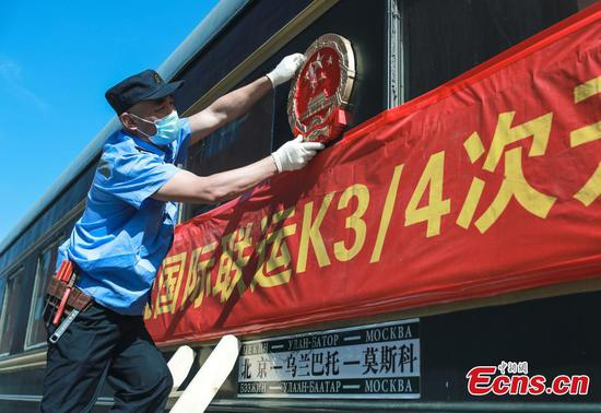 A staff member hangs the national emblem after an overhaul of the K3/4 train in Beijing on May 19, 2020. (Photo: China News Service/Jia Tianyong)