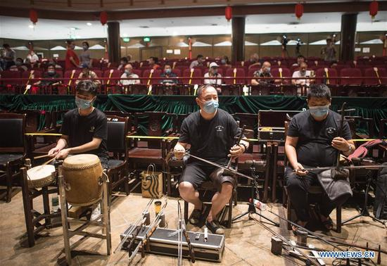 Staff members make preparations before a performance at Renmin theater in Wuhan, central China's Hubei Province, June 26, 2020. Seven theaters reopened to the public on Friday in Wuhan. (Xinhua/Xiao Yijiu)