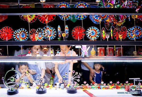 Tourists buy souvenirs at a shop in the Jimo ancient city of Qingdao, east China's Shandong Province, July 25, 2020. (Photo by Liang Xiaopeng/Xinhua)