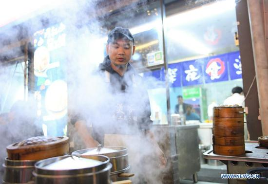 A staff member works in a restaurant at a night market in Shouchang Township of Jiande City, east China's Zhejiang Province, Nov. 10, 2020. Shouchang, a small town in mountainous area of Zhejiang, has set up a special night market bringing together night-time booths and more than 30 restaurants, in an effort to enrich people's leisure time and boost local economy. The night market has received over 720,000 tourist trips and raked in 76.33 million yuan (about 11.57 million U.S. dollars) since it opened during the Labor Day holiday. (Xinhua/Weng Xinyang)