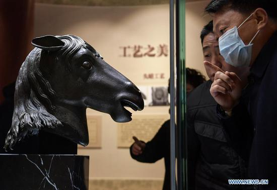 Visitors view a bronze horse head sculpture looted from Yuanmingyuan which is on display at Wenshu Pavilion of Zhengjue Temple in Yuanmingyuan, Beijing, capital of China, Dec. 1, 2020. A bronze horse head sculpture, a treasure of China's Old Summer Palace that went missing after an Anglo-French allied forces' looting 160 years ago, returned to its original palace home Tuesday. It is the first time that a lost important cultural relic from the Old Summer Palace, or