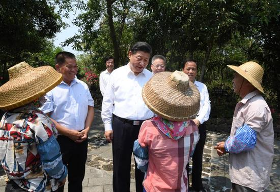Chinese President Xi Jinping, also general secretary of the Communist Party of China Central Committee and chairman of the Central Military Commission, talks with villagers in Shicha Village of Xiuying District in Haikou, south China's Hainan Province, April 13, 2018. Xi made an inspection tour in Hainan from Wednesday to Friday. (Xinhua/Li Xueren)