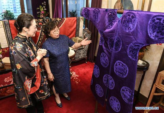 Researcher Fan Hongqi (R) introduces a men's costume of early Qing Dynasty (1644-1911) during an exhibition of traditional costumes and embroidery artworks in Beijing, capital of China, June 3, 2018. (Xinhua/Li He)