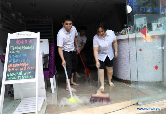 Staff of a shop drain the floodwater in Haikou, south China's Hainan Province, Aug. 10, 2018. Hainan was hit by heavy rainfalls under the influence of a tropical depression on Friday, which triggered a red alert for rainstorms in seven cities and counties, including Haikou. (Xinhua/Wang Junfeng)