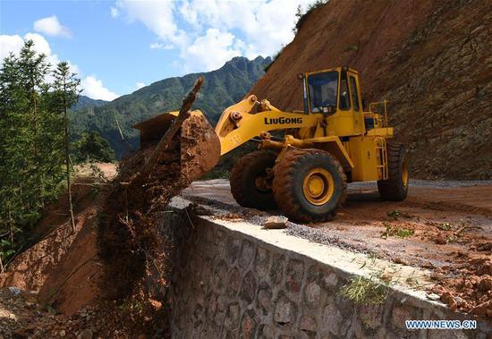 A worker clears a road damaged by Typhoon Mangkhut in Liuxiang Village of the Yao Autonomous County of Jinxiu in south China's Guangxi Zhuang Autonomous Region, Sept. 19, 2018. (Xinhua/Lu Boan)