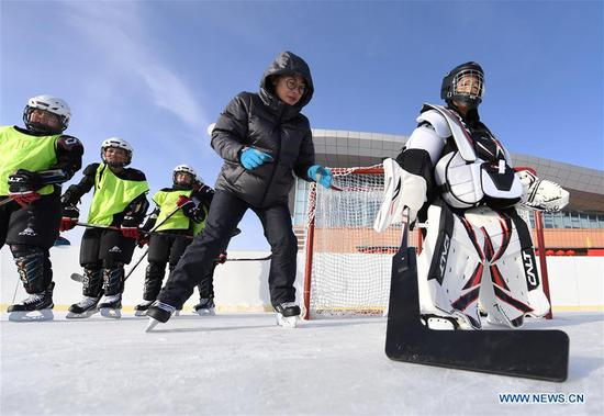 Zhou Xiaofeng (2nd R), coach of the ice hockey team of Wenyun County Primary School trains the goalkeeper Li Runtao (1st R) in Fuyun County of Altay, northwest China's Xinjiang Uygur Autonomous Region, Jan 18, 2019. Wenyun County Primary School established their ice hockey team in 2013, the first campus ice hockey team in Altay, with the help of the Charles Wang Ice Hockey Hope Project. There are 50 players aging 10 to 14 in the team at present. Altay is enhancing local winter sports and fitness programs for its rich ice and snow resources, such as ice hockey, ice soccer, skiing and skating. (Xinhua/Sadat)