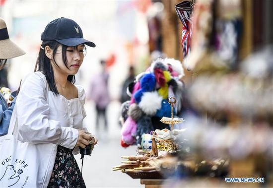 A tourist visits the Xinjiang International Grand Bazaar in Urumqi, capital of northwest China's Xinjiang Uygur Autonomous Region, April 4, 2019. The market, which has witnessed a booming tourism, received about 1.33 million visits in March alone. (Xinhua/Wang Fei)