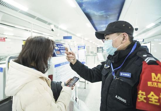 A staff member checks a passenger's body temperature at Wangjiadun metro station in Wuhan, 9 a.m. Jan. 23, 2020. (Xinhua/Xiao Yijiu)