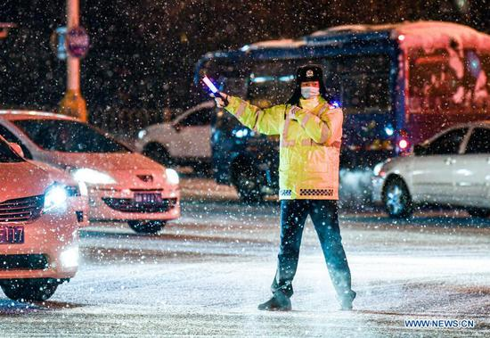 A police officer is on duty amid snowfall in Urumqi, capital of northwest China's Xinjiang Uygur Autonomous Region, Nov. 19, 2019. Days of continuous snowfall has left streets wet and slippery in the city of Urumqi. (Xinhua/Wang Fei)