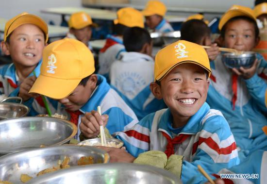 File photo taken on June 10, 2014 shows students having lunch at a primary school in Pozhang Township of Shannan, southwest China's Tibet Autonomous Region. The Chinese government has, so far, spent more than 20 billion yuan on supporting the region's free education program, making education more accessible for nearly nine million students. Students across all grades can also access additional support through a number of projects and initiatives under 40 educational aid projects, providing grants and scholarships, among others. (Xinhua/Chogo)
