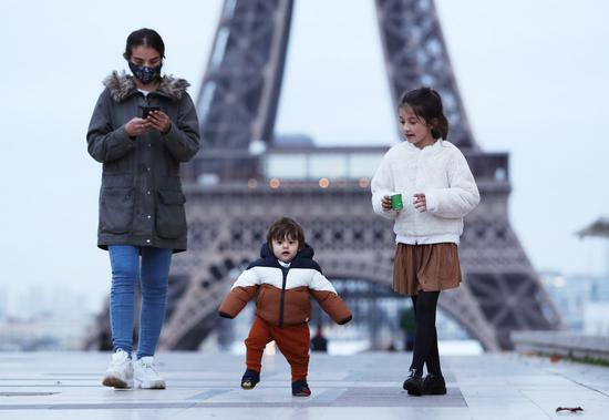 A mother and her children take a walk at the Trocadero Square near the Eiffel Tower, in Paris, France, Nov. 16, 2020. (Xinhua/Gao Jing)