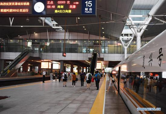 Passengers get off a Fuxing bullet train from Beijing at Tianjin Railway Station, in Tianjin, north China, Aug 8, 2018. The speed of Fuxing bullet trains running on the Beijing-Tianjin intercity rail increased to 350 km per hour Wednesday, cutting the journey to 30 minutes. (Xinhua/Zhang Chenlin)