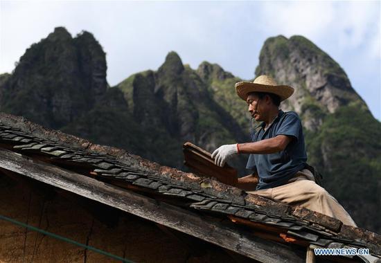 A villager repairs a roof damaged by Super Typhoon Mangkhut in Shijia Village of the Yao Autonomous County of Jinxiu in south China's Guangxi Zhuang Autonomous Region, Sept. 19, 2018. (Xinhua/Lu Boan)