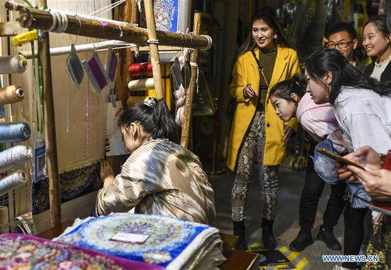 Tourists watch a store owner weaving a carpet at the Xinjiang International Grand Bazaar in Urumqi, capital of northwest China's Xinjiang Uygur Autonomous Region, April 4, 2019. The market, which has witnessed a booming tourism, received about 1.33 million visits in March alone. (Xinhua/Wang Fei)