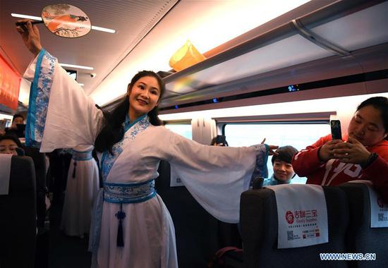 Staff members perform onboard the first high-speed train G7787 running from Fuyangxi Railway Station to Shanghai Hongqiao Railway Station, Dec. 1, 2019. High-speed railway line linking Shangqiu and Hefei, as well as a section linking Zhengzhou and Fuyang, was put into operation on Sunday. (Xinhua/Liu Junxi)