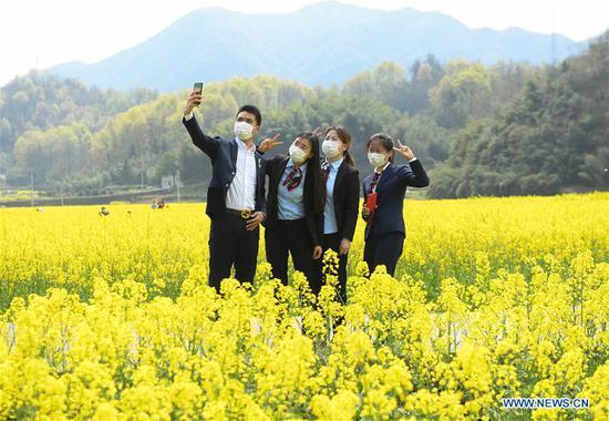Tourists take selfie at a cole flower field in Zhuji, east China's Zhejiang Province, March 17, 2020. (Xinhua/Weng Xinyang)
