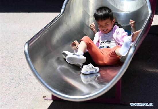 A child plays on a slide in Haidian District of Beijing, capital of China, May 31, 2020. (Xinhua/Zhang Chenlin)
