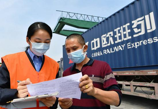 Li Ying (L), staff member with Haicang Station of China Railway Nanchang Group Co., Ltd. checks medical supplies as well as electronic devices and clothes that will be loaded onto a China-Europe freight train bound for Hamburg of Germany at Haicang Station in Xiamen, southeast China's Fujian Province, April 25, 2020. (Xinhua/Wei Peiquan)